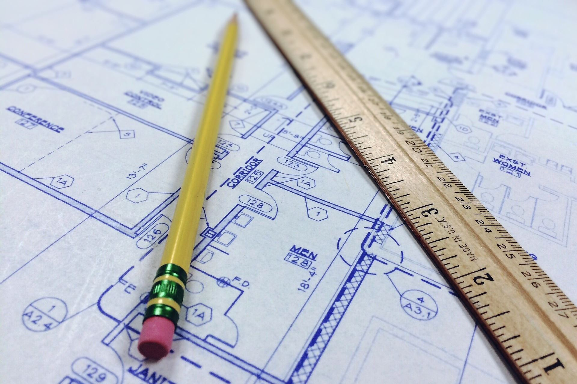 Ruler and pencil sitting on top of a building blueprint