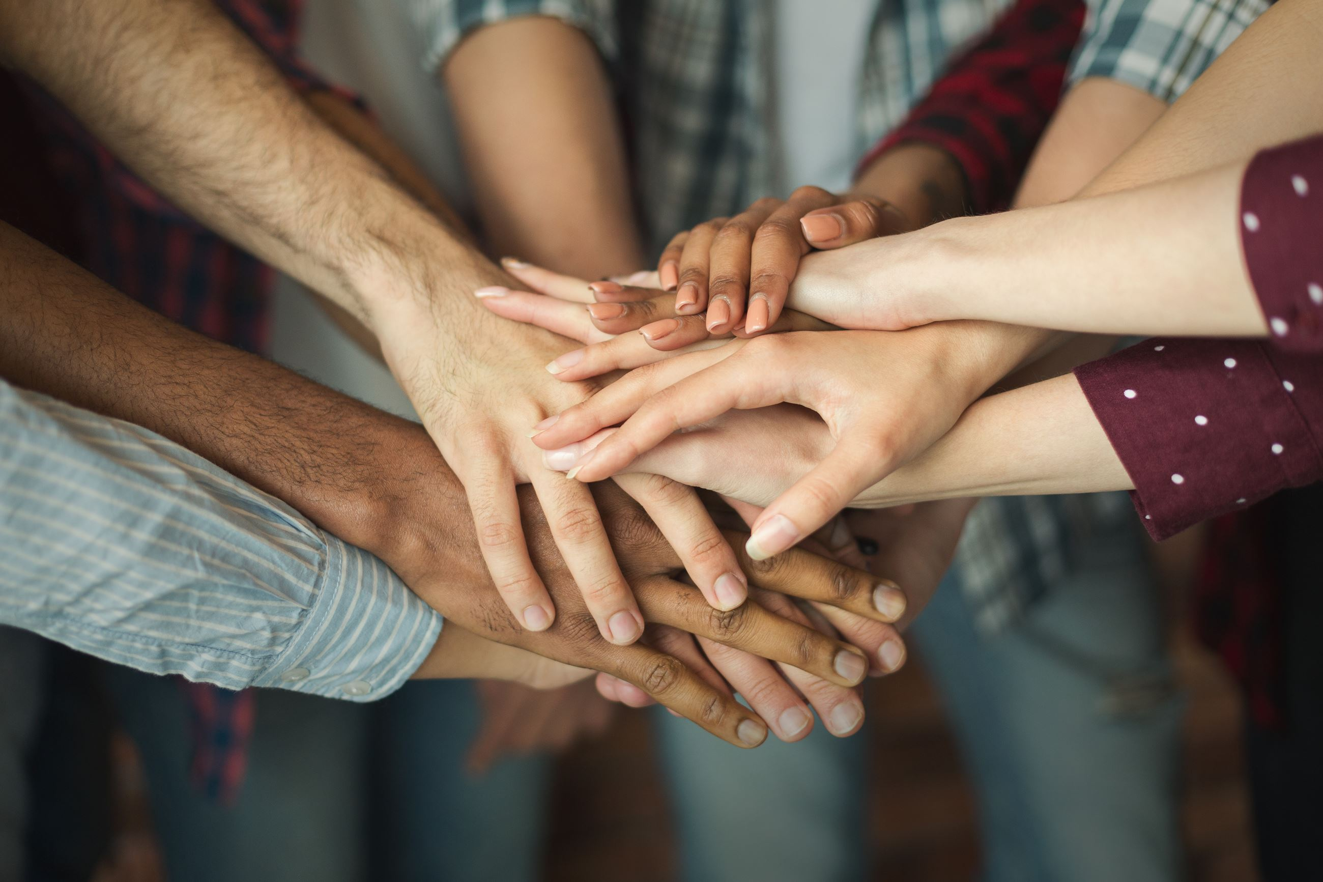 Close-up photo of a huddle of people piling hands on top of one another.