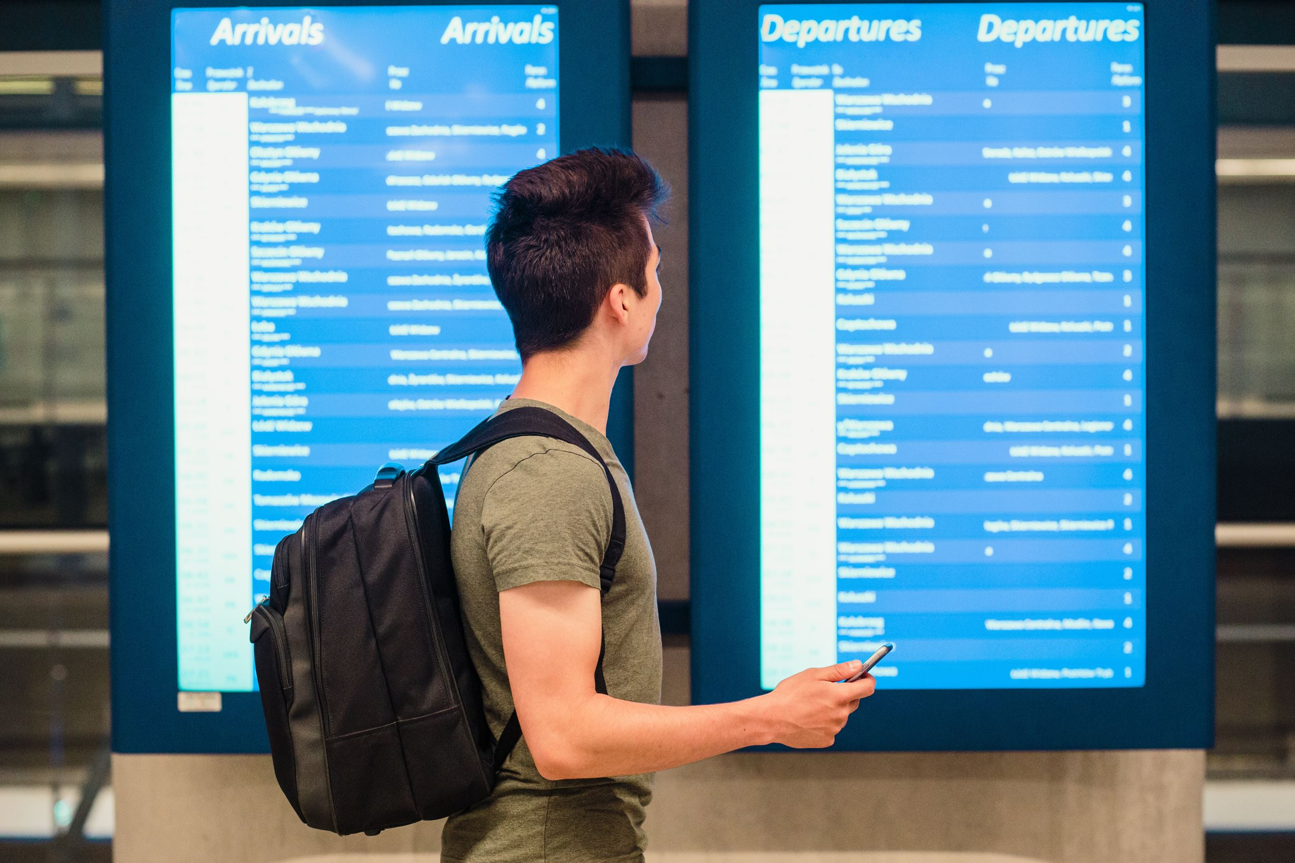 Young man standing in the bus and train station next to screens with schedule and planning a trip